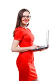 Стоящая молодая взрослая женщина в красных платье & стеклах держа компьютерное компьтер-книжки изолированный над белой предпосылк Стоковые Изображения