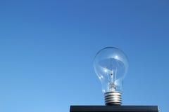 Стоящая электрическая лампочка в голубом небе Стоковое Изображение
