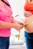 Стоящие беременные женщины и окружность повитухи измеряя b Стоковые Изображения RF