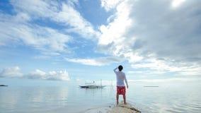Стоящий молодой человек смотрит горизонт на пляже Стоковые Фото