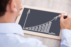 Столбиковая диаграмма чертежа бизнесмена на шифере на столе Стоковая Фотография