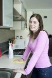 Столешница привлекательной девушки полируя на кухне и усмехаться Стоковая Фотография