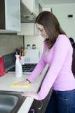 Столешница привлекательной девушки полируя на кухне Стоковые Фотографии RF