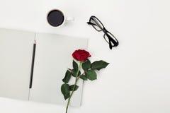 Стол женщины работая с чашкой кофе утра, карандашем, пустой тетрадью, стеклами и розовым цветком на белой таблице сверху Плоское  Стоковое Изображение RF