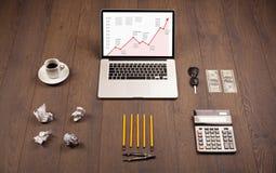 Стол компьютера с компьтер-книжкой и красная диаграмма стрелки в экране Стоковое Изображение