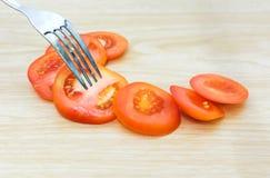 Столовый прибор и свежие томаты на деревянной предпосылке Стоковое фото RF