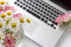 Стол офиса женщины с цветками цветения стоковое изображение rf