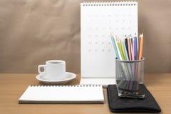 Стол офиса: кофе с телефоном, бумажником, календарем, коробкой карандаша цвета Стоковые Изображения