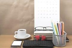 Стол офиса: кофе с телефоном, бумажником, календарем, коробкой карандаша цвета Стоковая Фотография
