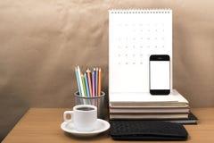 Стол офиса: кофе с телефоном, бумажником, календарем, коробкой карандаша цвета Стоковое Фото