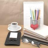 Стол офиса: кофе с телефоном, бумажником, календарем, коробкой карандаша цвета Стоковое фото RF