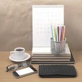 Стол офиса: кофе с телефоном, бумажником, календарем, коробкой карандаша цвета Стоковые Фото