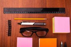 Стол офиса с стеклами пишет правителю карандаша и другим деталям офиса Стоковые Изображения