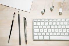 Стол офиса с cabl наушника и usb карандаша бумаги ручки клавиатуры Стоковые Изображения