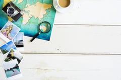 Стол путешественника с сложенной бумажной картой мира и фото Стоковое Изображение RF