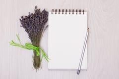 Стол с насмешкой взгляд сверху лаванды цветков вверх Раскройте sketchbook Тетрадь Стоковые Изображения