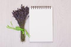 Стол с насмешкой взгляд сверху лаванды цветков вверх Раскройте sketchbook Тетрадь Стоковые Изображения RF