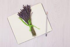 Стол с насмешкой взгляд сверху лаванды цветков вверх Раскройте sketchbook Тетрадь Стоковое Изображение