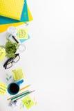 Стол с поставками зеленого цвета, пустой блокнот таблицы офиса, чашка, ручка, стекла, скомкал бумагу, лупу, цветок дальше Стоковые Фотографии RF