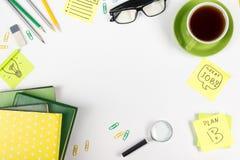 Стол с поставками зеленого цвета, пустой блокнот таблицы офиса, чашка, ручка, стекла, скомкал бумагу, лупу, цветок дальше Стоковое Фото