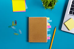 Стол таблицы офиса с комплектом красочных поставек, белым пустым блокнотом, чашкой, ручкой, ПК, скомкал бумагу, цветок на сини Стоковые Фотографии RF