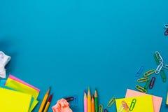 Стол таблицы офиса с комплектом красочных поставек, белым пустым блокнотом, чашкой, ручкой, ПК, скомкал бумагу, цветок на сини Стоковая Фотография