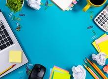 Стол таблицы офиса с комплектом красочных поставек, белым пустым блокнотом, чашкой, ручкой, ПК, скомкал бумагу, цветок на сини Стоковые Фото