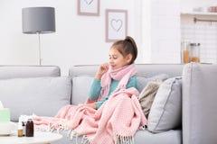 Страдание маленькой девочки от кашля и холод на софе стоковые изображения rf