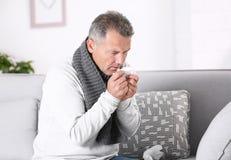 Страдание человека от кашля и холод на софе стоковые фото