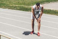 страдая молодой бегун с положением травмы ноги стоковое фото rf