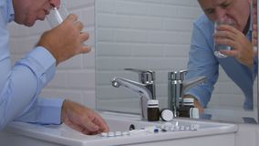 Страдая человек выбирает и принимает таблетки от раковины Bathroom стоковые фото