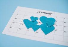Страница календаря в феврале с голубыми чувствуемыми сердцами около 14 на пастельной голубой предпосылке с космосом экземпляра стоковые изображения