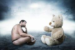 Странный нагой человек смотрит медведя игрушки Стоковая Фотография RF