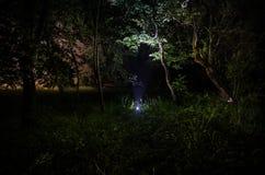 Странный силуэт в темном пугающем лесе на ноче, светах мистического ландшафта сюрреалистических с страшным человеком Стоковая Фотография RF