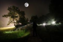 Странный силуэт в темном пугающем лесе на ноче, светах мистического ландшафта сюрреалистических с страшным человеком Стоковое Изображение