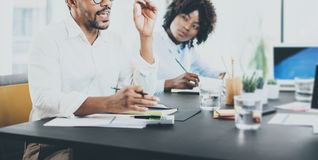 Стратегия бизнеса бизнесмена чёрного африканца explaning в конференц-зале 2 молодых предпринимателя работая совместно в a Стоковые Изображения