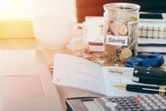 Страхование автомобилей и концепция займа: Ключ автомобиля на банке книги на столе с сбережениями денег в банке монетки опарника, Стоковое Фото