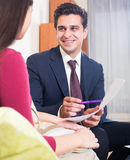Страховой инспектор и клиент обсуждая условия согласования в livin Стоковая Фотография RF