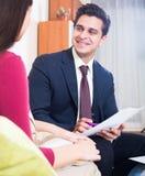 Страховой инспектор и клиент обсуждая условия согласования в livin Стоковое Изображение