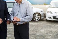 Страховой инспектор рассматривает поврежденное signatur опиловки автомобиля и клиента стоковые фото