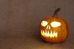 Страшная накаляя сторона тыквы Страшная тыква хеллоуина на предпосылке мешковины Стоковые Фотографии RF