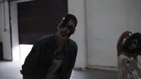 Страшная сцена мужчины 2 и женских зомби приходя дальше в пустое размещение с белыми стенами Хеллоуин, киносъемка, сцена видеоматериал