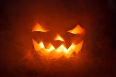 Страшная тыква хеллоуина смотря через дым. Стоковое Фото