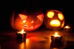 Страшные Джек-o-фонарики тыквы и дыни хеллоуина на черной предпосылке осветили с малым кругом и свечами звезды Стоковые Изображения RF