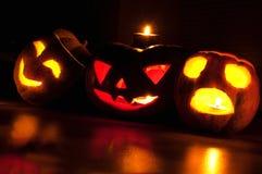 Страшные Джек-o-фонарики тыквы и дыни хеллоуина на черной предпосылке осветили с малым кругом и свечами звезды Стоковое Изображение