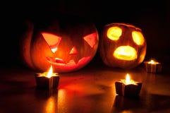 Страшные Джек-o-фонарики тыквы и дыни хеллоуина на черной предпосылке осветили с малым кругом и свечами звезды Стоковое Фото