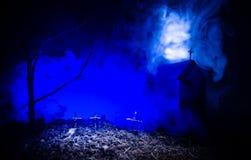 Страшный взгляд зомби на дереве кладбища мертвом, луне, церков и пугающем облачном небе с туманом, концепцией хеллоуина ужаса Стоковая Фотография