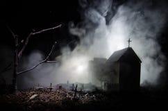Страшный взгляд зомби на дереве кладбища мертвом, луне, церков и пугающем облачном небе с туманом, концепцией хеллоуина ужаса Стоковое Фото