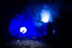 Страшный взгляд зомби на дереве кладбища мертвом, луне, церков и пугающем облачном небе с туманом, концепцией хеллоуина ужаса Стоковое Изображение