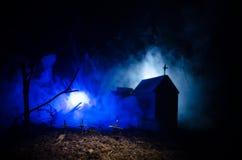 Страшный взгляд зомби на дереве кладбища мертвом, луне, церков и пугающем облачном небе с туманом, концепцией хеллоуина ужаса Стоковое фото RF